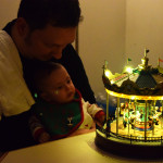 Hazel watches the musical merry go round with daddy.