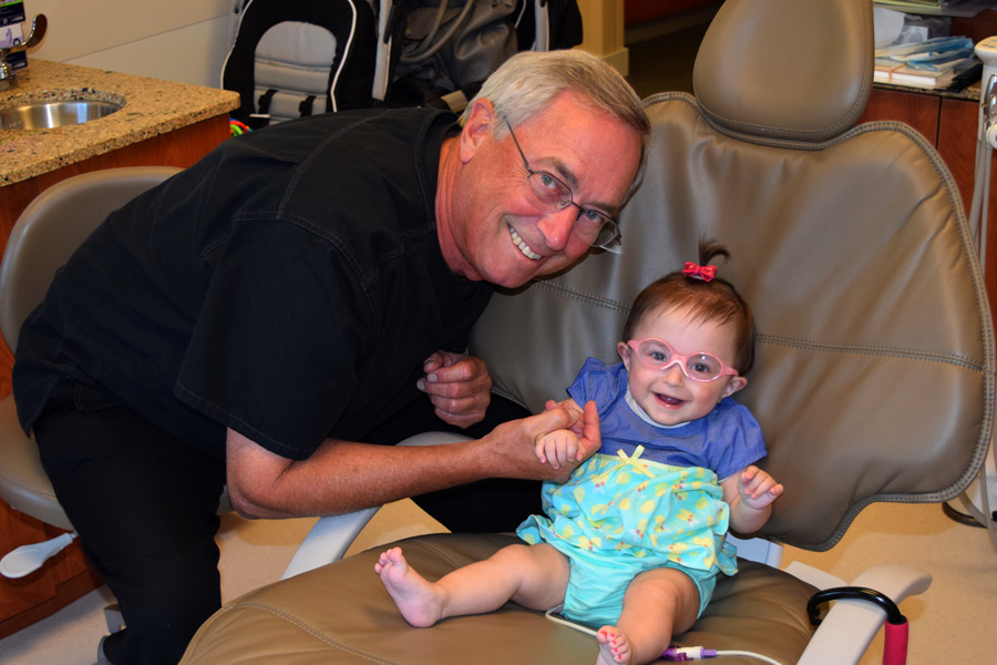 Hazel getting her first dental checkup from Grandpa.